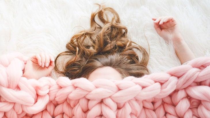 Woman in bed under blanket
